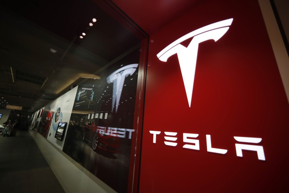 "FILE- In this Feb. 9, 2019, file photo, a sign bearing the company logo is displayed outside a Tesla store in Cherry Creek Mall in Denver. The U.S. government's highway safety agency says it's gathering information on reports of malfunctions with a Tesla feature that lets drivers summon their cars in parking lots. The National Highway Traffic Safety Administration says it's aware of reports about ""Smart Summon"" and is in contact with the company. Messages were left Thursday seeking comment from Tesla. (AP Photo/David Zalubowski, File) Tesla store,tesla logo"