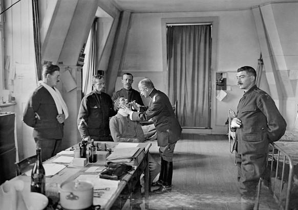 ZUR SDA-SERIE ZUM THEMA 100 JAHRE ERSTER WELTKRIEG VOM FREITAG, 18. JULI 2014, STELLEN WIR IHNEN FOLGENDES ARCHIVBILD ZUR VERFUEGUNG - Ein Truppenarzt untersucht waehrend des Ersten Weltkrieges 1914 - 1918 Schweizer Armeeangehoerige in einem Krankenzimmer . Die eigentliche Bewaehrungsprobe der Truppensanitaet kam mit der Epidemie der Spanischen Grippe. Die Zahl der Opfer war gross, bei den Etappensanitaetsanstalten standen Militaerspiele bereit, um den Toten mit Chopins Trauermarsch das letzte Geleit zur Fahrt nach den heimatlichen Friedhoefen zu geben. (KEYSTONE/Photopress-Archiv/Str)  *** ONE TIME USE ONLY, BLACK AND WHITE ONLY ***