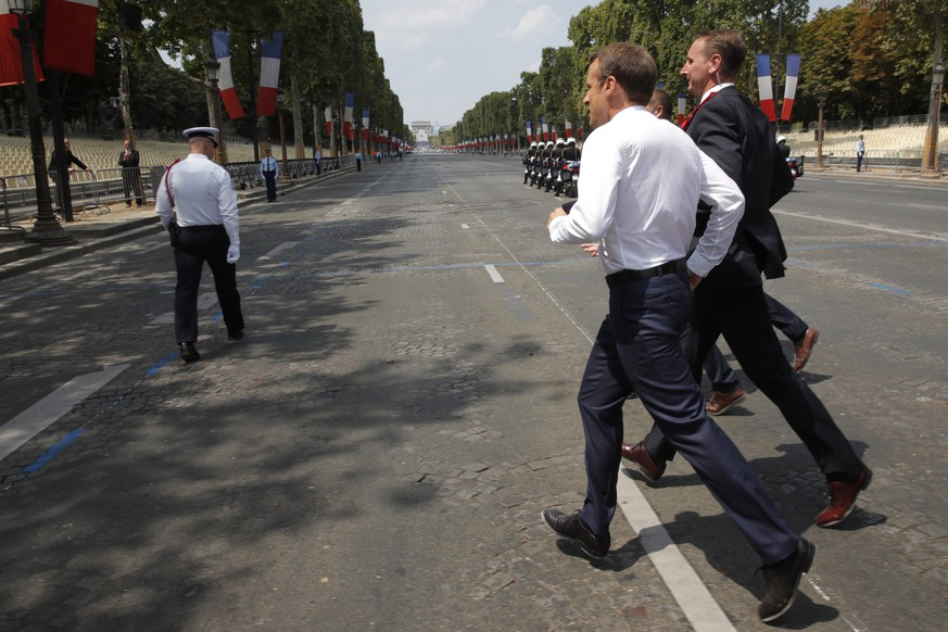 epa06888152 French President Emmanuel Macron runs to greet people after the traditional Bastille Day military parade on the Champs-Elysees avenue in Paris, France, 14 July 2018.  EPA/PHILIPPE WOJAZER / POOL MAXPPP OUT