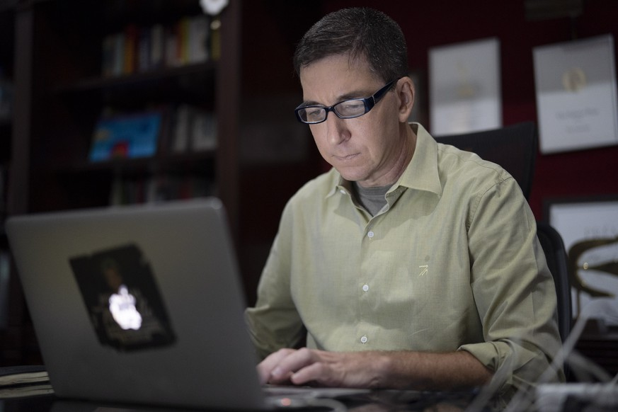 FILE - In this July 10, 2019 file photo, U.S. journalist Glenn Greenwald checks his news website at his home in Rio de Janeiro, Brazil. Brazilian prosecutors accused Greenwald on Tuesday, Jan. 21, 2020, of involvement in hacking the phones of Brazilian officials involved in a corruption investigation, though Brazil's high court had blocked investigations of the journalist or his Brazil-based news outlet in relation to the case. (AP Photo/Leo Correa, File) Glenn Greenwald