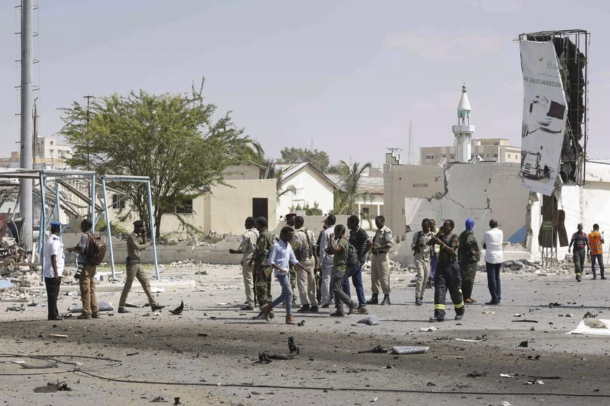 epa07244421 Somali security officers gather at the scene of twin explosions near the National Theater in Mogadishu, Somalia, 22 December 2018. A suicide car bomb reportedly exploded at a checkpoint near the National Theater followed by another explosion nearby, killing several people, according to local media. Initial reports suggest that at least six people were killed and more than 13 others were injured in the incident. The country's Islamist militant group al-Shabab often carries out similar attacks in the country to topple the western-backed government.  EPA/SAID YUSUF WARSAME
