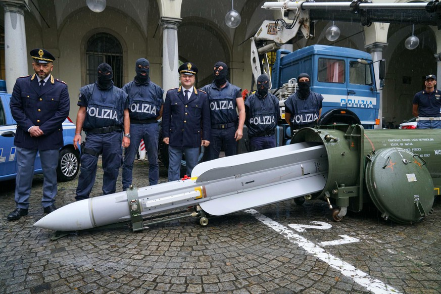 Police stand by a missile seized at an airport hangar near Pavia, northern Italy, following an investigation into Italians who took part in the Russian-backed insurgency in eastern Ukraine, in Turin, Italy, Monday, July 15, 2019. Police in northern Italy have detained three men, including one tied to a neo-fascist Italian political party, after uncovering a huge stash of automatic weapons, a missile and Nazi propaganda. (Tino Romano/ANSA via AP)