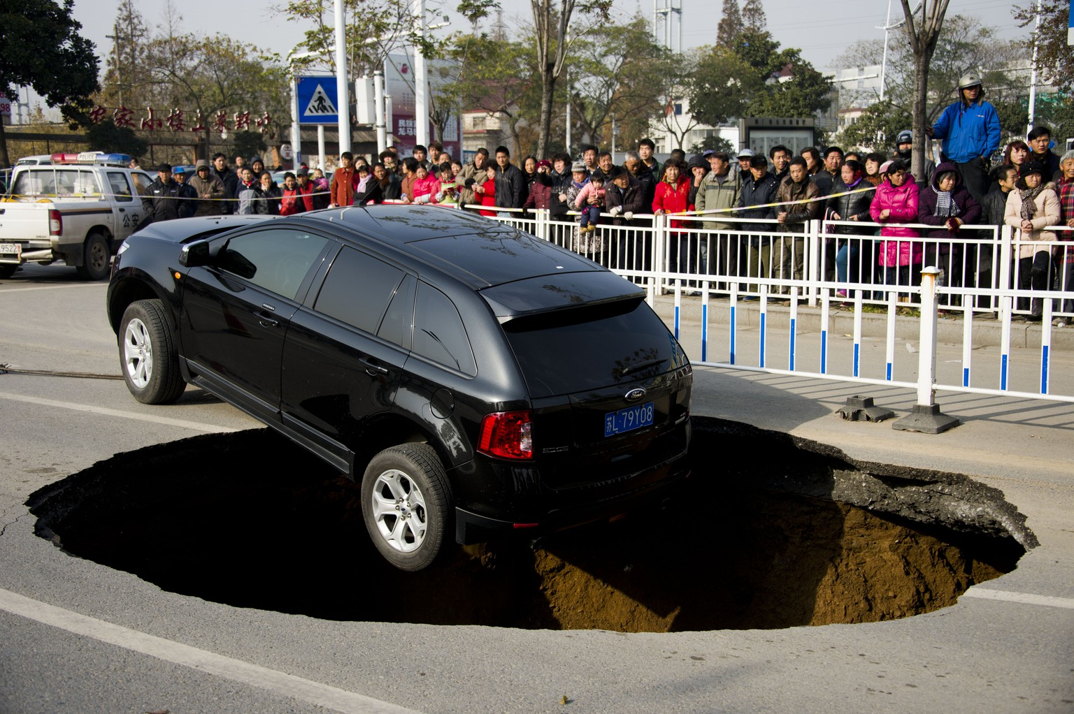 ZHENJIANG, CHINA - DECEMBER 12:  A Ford sedan car halts on the verge of a five meters wide and two meters deep hole at Yunlianghe Road on December 12, 2014 in Zhenjiang, Jiangsu Province of China. A Ford sedan car halted on the verge of a hole at Yunlianghe Road after the road collapsed and formed a five meters wide and two meters deep hole abound 8 o'clock on Friday morning. The road was just opened for two years and the reason is still under investigation.  (Photo by ChinaFotoPress/ChinaFotoPress via Getty Images)