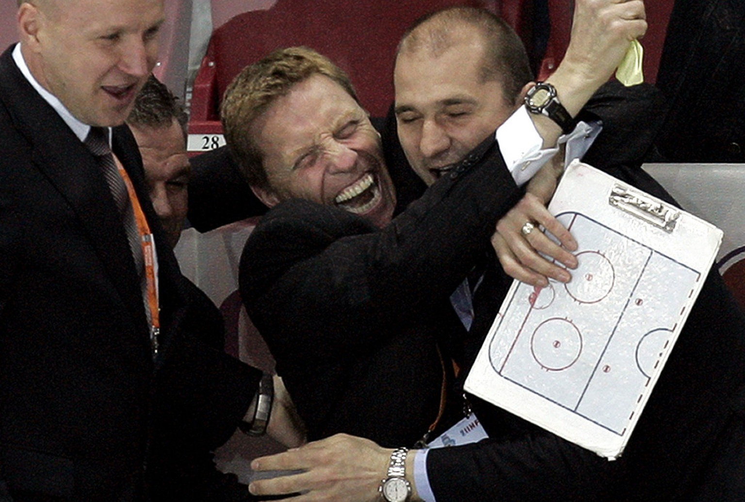 Belarus' head coach Glen Hanlon, center, of the Washington Capitals, and other team officials celebrate their 2-1 victory over Switzerland at the IIHF Ice Hockey World championship match in the Latvian capital Riga Tuesday, May 16, 2006. (KEYSTONE/AP Photo / Ivan Sekretarev)