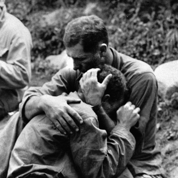 An American infantryman, his buddy killed in action in the Korean War, weeps on the shoulder of another GI somewhere in Korea, August 28, 1950. Meanwhile, a corpsman, left, goes about the business of filling out casualty tags. No identifications available. (KEYSTONE/AP Photo/Stf) === ===