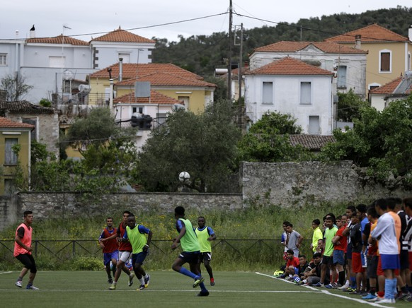 In this Saturday, May 4, 2019, African team and Afghan migrants play a friendly game at a soccer field, in Moria village, on the northeastern Aegean island of Lesbos, Greece. A 10-minute walk from Europe's largest refugee camp is a place where residents of the Moria camp on the Greek island of Lesbos can briefly forget about their tiny container-homes and crowded tents and instead worry about corner kicks and throw-ins. Many of the players hope to turn professional and leave the camp, where they are forced to remain indefinitely under European Union rules designed to limit the number of migrants and refugees reaching the mainland. (AP Photo/Thanassis Stavrakis)