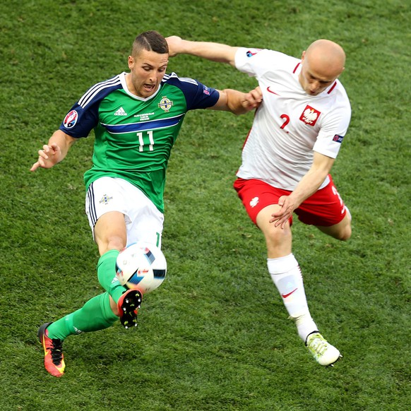 epa05359777 Conor Washington of Northern Ireland (L) and Michal Pazdan of Poland in action during the UEFA EURO 2016 group C preliminary round match between Poland and Northern Ireland at Stade de Nice in Nice, France, 12 June 2016.