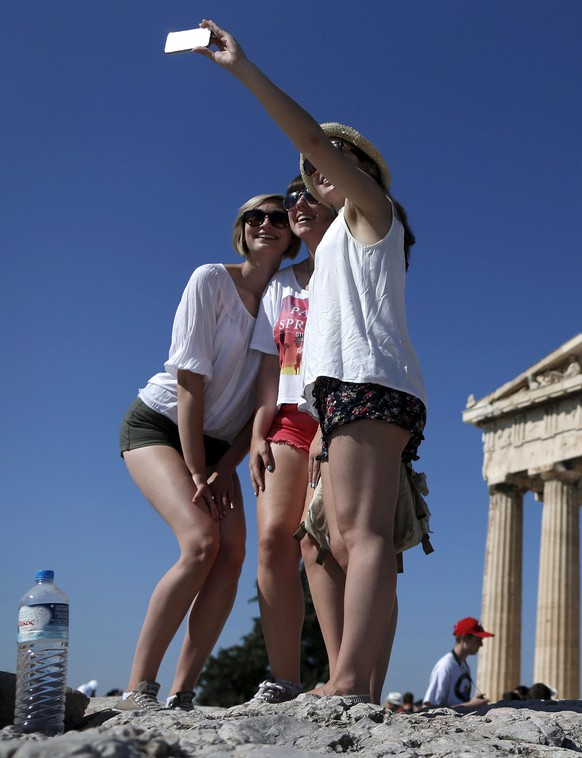 A group of tourists take a selfie in front of the temple of the Parthenon atop the Acropolis in Athens, Greece July 9, 2015. A race to save Greece from bankruptcy and keep it in the euro gathered pace on Wednesday when Athens formally applied for a three-year loan and European authorities launched an accelerated review of the request. REUTERS/Christian Hartmann