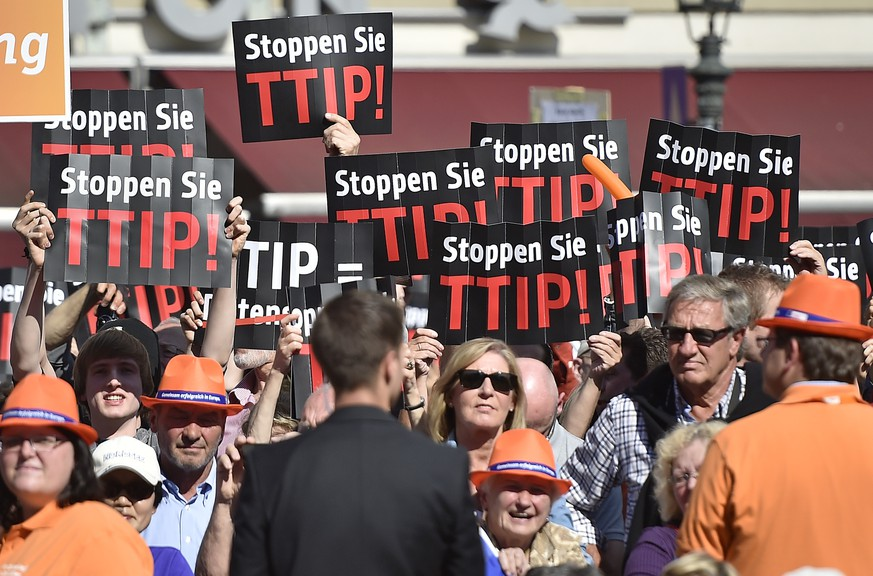 People protest against the Transatlantic Trade and Investment Partnership (TTIP) with the USA at the final election party of the Christian Democratic Union (CDU) prior Sunday's EU Parliament elections in Duesseldorf, Germany, Friday, May 23, 2014. (AP Photo/Martin Meissner)