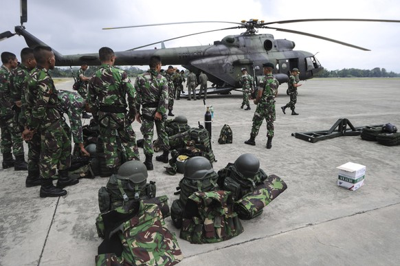 In this photo released by China's Xinhua News Agency, soldiers prepare to leave for the crash site of an Indonesian passenger plane for rescue operations at an air base in Jayapura, Indonesia Tuesday, Aug. 18, 2015. The Indonesian passenger plane that went missing two days ago was destroyed when it slammed into a mountain, killing all people on board, the country's top rescue official said. (Veri Sanovri/Xinhua via AP) NO SALES
