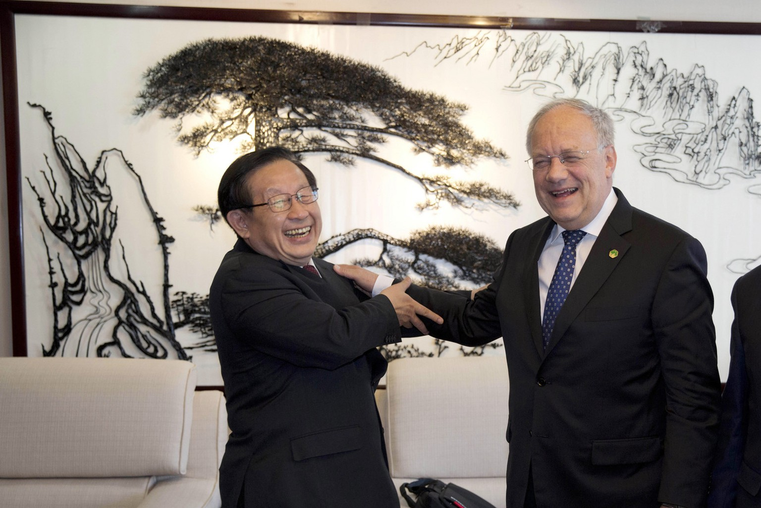 Switzerland's Federal President Johann Schneider-Ammann, right, enjoys a moment with China's Minister of Science and Technology Wan Gang during a visit to the ministry in Beijing, China, Friday, April 8, 2016. (AP Photo/Ng Han Guan)