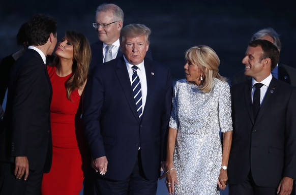 epa07794923 Canadian Prime Minister Justin Trudeau (L) embraces US First Lady Melania Trump (2-L) as US President Donald J. Trump (C), French President Emmanuel Macron (R) and his wife Brigitte (2-R) look on as they attend the family photo during the G7 summit at Casino in Biarritz, France, 25 August 2019, issued 26 August 2019. The G7 Summit runs from 24 to 26 August in Biarritz.  EPA/IAN LANGSDON
