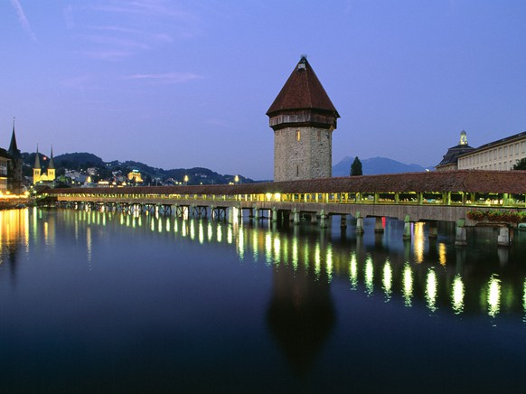 View of the Kapellbruecke bridge in Lucerne, Switzerland, pictured on August 2, 2003. The bridge was built as a guard's walkway in the 14th century and is Europe's oldest wooden bridge. Inside the bridge are 111 paintings depicting events of Switzerland's history. Parts of the bridge and of the paintings were destroyed by a fire in 1993, though it was quickly rebuilt. (KEYSTONE/Martin Ruetschi)Blick auf die Kapellbruecke in Luzern, aufgenommen am 2. August 2003. Die Bruecke wurde im 14. Jahrhundert als Wehrgang erbaut und ist die aelteste Holzbruecke Europas. Im Giebel der Bruecke befinden sich 111 dreieckige Gemaelde, die wichtige Szenen der Schweizer Geschichte darstellen. 1993 brannte die Kapellbruecke teilweise ab, wurde aber wieder aufgebaut. (KEYSTONE/Martin Ruetschi)