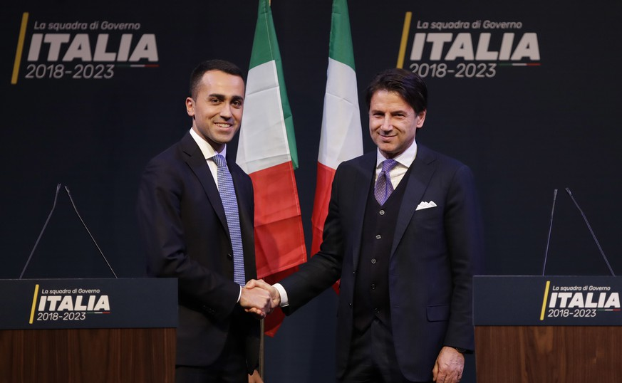 In this photo taken on Thursday, March 1, 2018, Giuseppe Conte, right, shakes hands with leader of the Five-Star Movement, Luigi Di Maio, during a meeting in Rome. Italy edged toward its first populist government Monday as the eurosceptic 5-Star Movement and the right-wing League indicated a 54-year-old law professor with no political experience as their candidate for premier. Neither 5-Star leader Luigi Di Maio nor League leader Matteo Salvini named Giuseppe Conte in brief remarks to reporters after leaving a closed-door meeting with President Sergio Mattarella in what could be final consultations before forming a government 11 weeks after elections left Italy with a hung parliament. But, in a breach of protocol, Di Maio identified Conte to reporters outside the Quirinale presidential palace and posted his name on the movement's popular block. (AP Photo/Alessandra Tarantino)