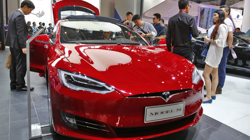 epa07295009 (FILE) - People look at a Tesla model S electric car on display at the Auto China 2016 motor show in Beijing, China, 26 April 2016 (reissued 18 January 2019). Tesla has issued a recall of more than 14,000 Model S cars in China after airbags were found to be fualty.  EPA/WU HONG