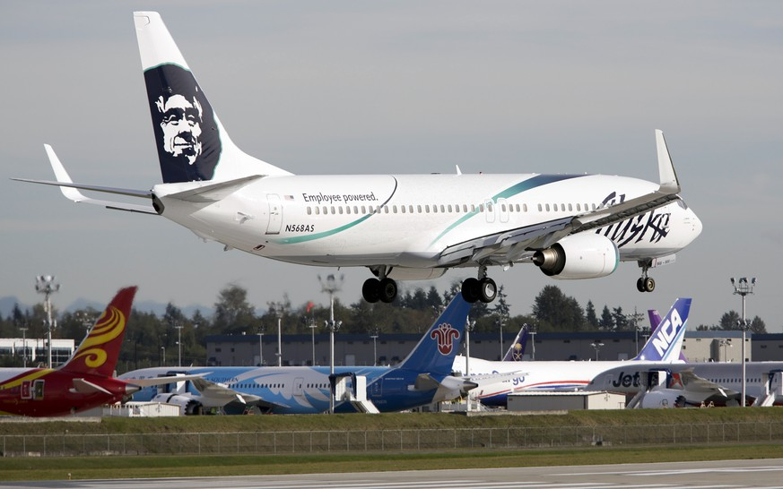 An Alaska Airlines passenger jet lands in front of a row of Boeing 787 Dreamliners at Paine Field Airport in Everett, Washington, in this file photo taken October 4, 2013.  A Los Angeles-bound Alaska Airlines flight made an emergency landing at a Seattle-area airport on Monday afternoon after it took off with a worker trapped in a cargo area under the cabin, the U.S. carrier said.  REUTERS/Jason Redmond/Files
