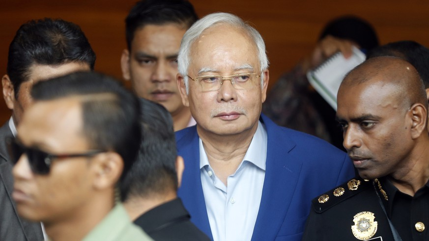 In this May 22, 2018, file photo, former Malaysian Prime Minister Najib Razak, center, arrives at Anti-Corruption Agency for questioning in Putrajaya, Malaysia. Malaysia's anti-graft agency says it has arrested former Najib over the multimillion-dollar looting of a state investment fund and that he will face further charges in court.  The agency says Najib was detained at its office on Wednesday, Sept. 14, and will be taken to court on Thursday to face the charges. (AP Photo/Vincent Thian)