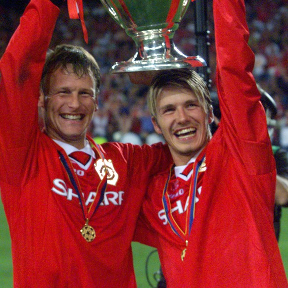 FILE - In this May 26, 1999, file photo, Manchester United's Teddy Sheringham, left, and David Beckham celebrate lift the trophy after defeating Bayern Munich 2-1 to win the Champions League soccer final in Barcelona, Spain. Manchester United took a few years to re-establish itself in European competition after the ban on English club participation was lifted. In 1999, United was going for a historic English treble when it met Bayern Munich. With the game already in injury time, any hope of adding the Champions League to the Premier League and FA Cup looked forlorn. However, in a stunning turnaround, goals from Sheringham and Ole Gunnar Solskjaer saw United win the trophy for the first time since 1968.(AP Photo/Camay Sungu, File)