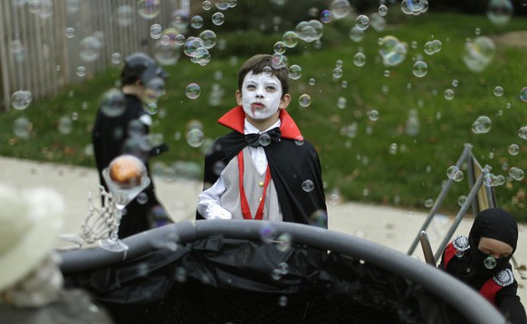 A boy dressed as Dracula looks at a bubble machine at the Flint family's annual Halloween block party in Silver Spring, Maryland October 31, 2014. The Flint family have decorated their house and thrown a theme block party for the last 17 years for neighborhood children and adults before the annual trick or treating.     REUTERS/Gary Cameron    (UNITED STATES - Tags: SOCIETY)