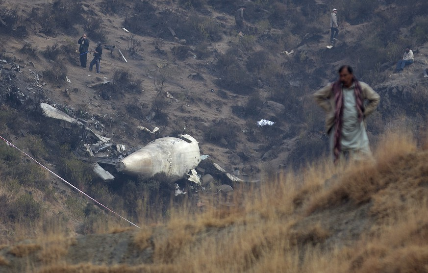CORRECTS NAME OF THE VILLAGE - A Pakistan villager stands at the site of plane crash as investigation is in progress in Gug near Havelian, Pakistan, Thursday, Dec. 8, 2016. Pakistan's national carrier Pakistan International Airlines (PIA) says the plane crashed shortly after takeoff from the northern city of Chitral with 48 people aboard. A spokesman for Pakistan's Civil Aviation Authority said Wednesday that the cause of the crash was unclear. (AP Photo/B.K. Bangash)