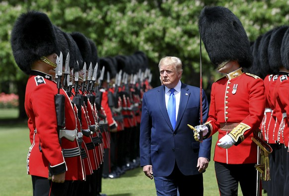 U.S President Donald Trump inspects an honour guard during a welcome ceremony in the garden of Buckingham Palace, in London, Monday, June 3, 2019, on the first day of a three day state visit to Britain. (Toby Melville/Pool via AP)
