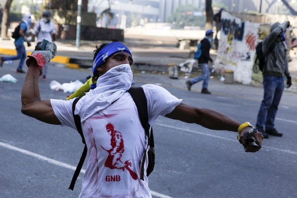 Anti-government protesters throw stones at the police during a protest against Nicolas Maduro's government in Caracas March 22, 2014. Two Venezuelans died from gunshot wounds during protests against socialist President Nicolas Maduro, witnesses and local media said on Saturday, pushing the death toll from almost two months of anti-government protests to 33. REUTERS/Carlos Garcia Rawlins (VENEZUELA - Tags: POLITICS CIVIL UNREST)