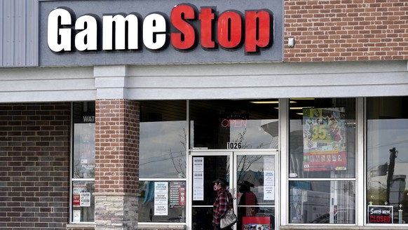 A woman wears a face mask as she walks past a GameStop store in Des Plaines, Ill., Thursday, Oct. 15, 2020. The latest battleground between the proletariat and the hedge funds serving the 1% isn