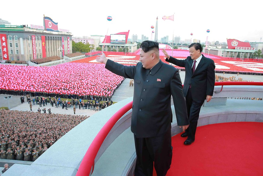 epa04974365 A picture released by the North Korean Central News Agency (KCNA) on 12 October 2015 shows North Korean leader Kim Jong-un (front) and Liu Yunshan, the Chinese Communist Party's fifth-ranked leader, waving to the crowd during a large-scale military parade at Pyongyang's Kim Il-sung Square, in Pyongyang, North Korea, 10 October 2015, to mark the 70th anniversary of the founding of the ruling Workers' Party of Korea.  EPA/KCNA -- BEST QUALITY AVAILABLE -- SOUTH KOREA OUT