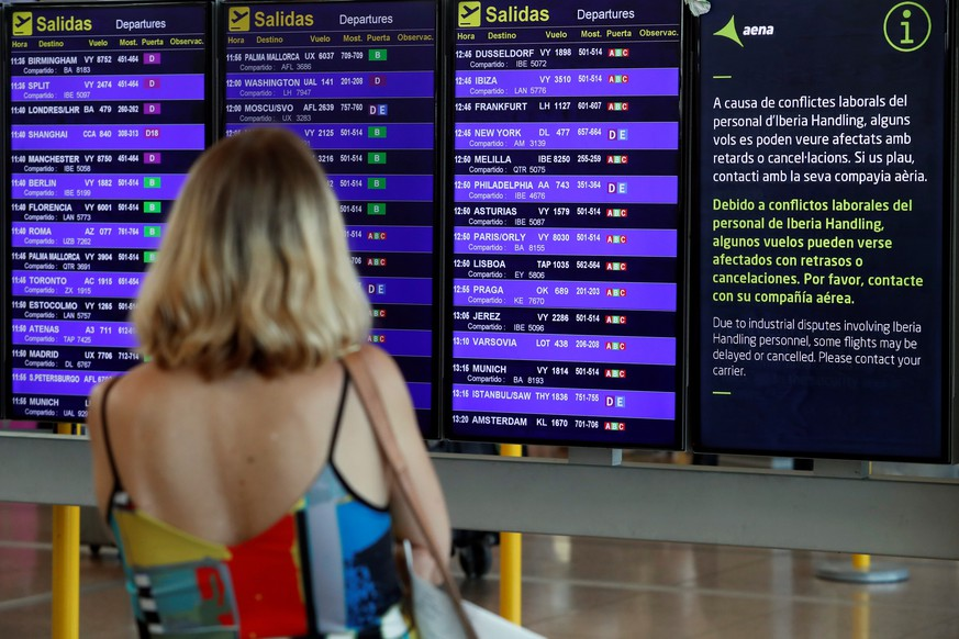 epa07806482 A woman checks her flight on a screen at El Prat airport in Barcelona, Spain, during the second day of strike held by Iberia's ground staff workers, 31 August 2019. According to the airline only 20 percent of their workers are following the strike that is being held in Madrid and Barcelona airports.  EPA/Toni Albir