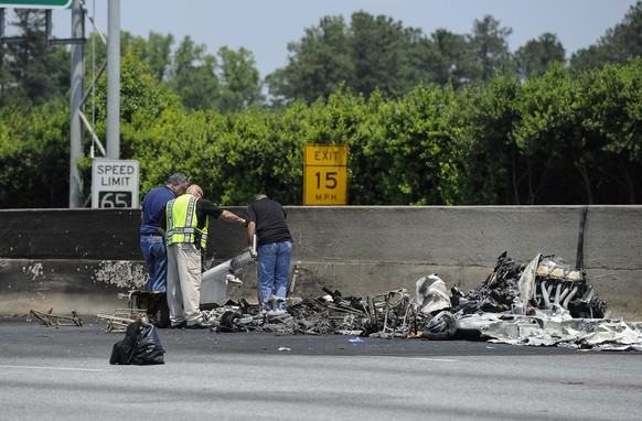 epa04738980 Investigators look over the wreckage of a plane crash in which four people were killed on Interstate 285 in Doraville, Georgia, USA, 08 May 2015. The crash which involved a Piper PA-32 taking off from Peachtree DeKalb Airport in route to Oxford Mississippi did not hit any vehicles.  EPA/JOHN AMIS