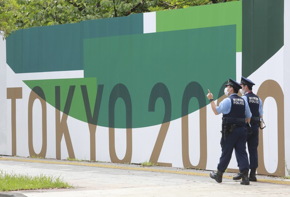 Police officers walk by posters to promote Tokyo 2020 Olympics in Tokyo, Wednesday, July 14, 2021. The Olympic Games are scheduled to begin on July 23. (AP Photo/Koji Sasahara)