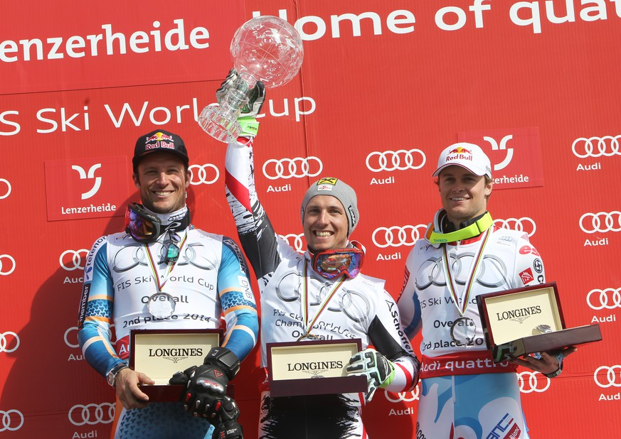Austria's Marcel Hirscher, center, alpine ski World Cup overall champion, celebrates on the podium with Norway's Aksel Lund Svindal, second overall champion, left, and France's Alexis Pinturault, third overall champion, at the alpine ski World Cup finals in Lenzerheide, Switzerland, Sunday, March 16, 2014.  (AP Photo/Armando Trovati)