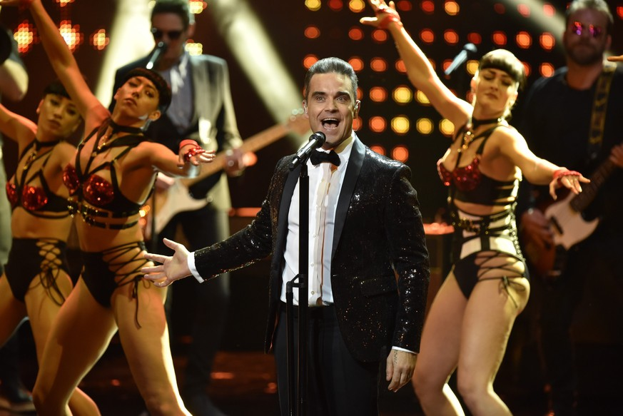 epa05635417 British musician Robbie Williams performs on stage at the 68th Bambi Award media awards ceremony in Berlin, Germany, 17 November 2016. The awards are the oldest media awards in Germany and are held annually to recognise excellence in international media and television.  EPA/CLEMENS BILAN