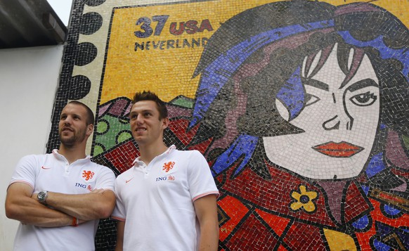 """Netherlands' national soccer team players Ron Vlaar (L) and Stefan de Vrij pose with a painting of the late pop star Michael Jackson during a visit to the Santa Marta slum in Rio de Janeiro, July 1, 2014. The painting was done in the area where Jackson filmed part of the Brazilian version of the """"They Don't Care About Us"""" music video in 1995.   REUTERS/Ricardo Moraes (BRAZIL  - Tags: SPORT SOCCER WORLD CUP SOCIETY POVERTY ENTERTAINMENT)"""