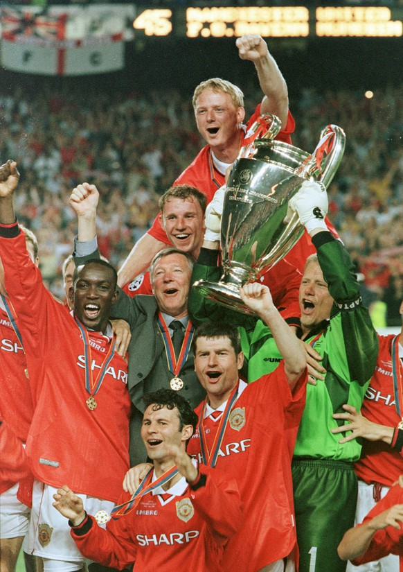 Manchester United team players celebrate with the trophy after winning the UEFA Champions League final at the Nou Camp Stadium in Barcelona on Wednesday, May 26, 1999. Manchester United beat Bayern Munich 2-1. (KEYSTONE/AP Photo/Cesar Rangel)