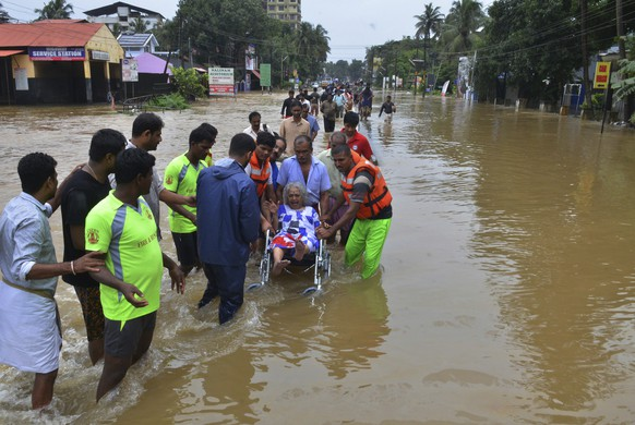 In this Thursday, Aug. 16, 2018 photo, an elderly woman is evacuated towards safer area in Thrissur, in the southern Indian state of Kerala. Rescuers used helicopters and boats on Friday to evacuate thousands of people stranded on their rooftops following unprecedented flooding in the southern Indian state of Kerala that left more than 100 dead. (AP Photo)