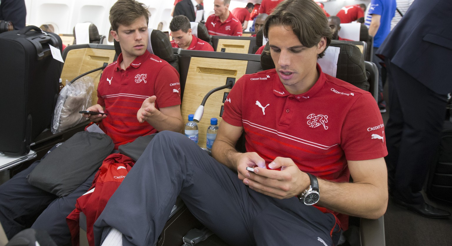Switzerland's Yann Sommer, right, and Valentin Stocker, left, operate their mobile phones prior to the start of the flight to Sao Paulo at the airport in Zuerich-Kloten, Switzerland, Friday, June 6, 2014. (KEYSTONE/Peter Klaunzer)