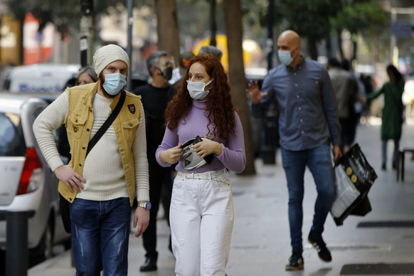 People wear masks to help protect themselves from the coronavirus on Hamra street in Beirut, Lebanon, Monday, Jan. 4, 2021. Lebanon is gearing up for a new nationwide lockdown, as officials vowed Monday to take stricter measures against the coronavirus following the holiday season, which saw a large increase in infections and caused jitters in the country's already-battered health sector. (AP Photo/Bilal Hussein) Hassan Diab