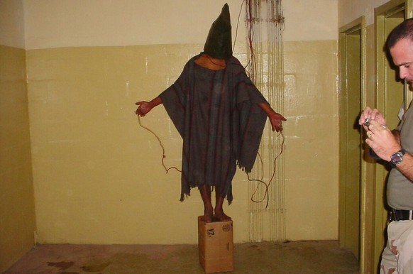 FILE - This late 2003 file photo, an image obtained by The Associated Press, shows an unidentified detainee standing on a box with a bag on his head and wires attached to him in the Abu Ghraib prison in Baghdad, Iraq. Amid violence like the attack in Paris on a satirical newspaper over its depictions of the Prophet Muhammad, there's been increasing discussions among Muslims who say their community must re-examine their faith to modernize its interpretations and sideline extremists. Cherif Kouachi, one of the French brothers behind the Charlie Hebdo killings, appears to have been first radicalized by hearing of abuses of Iraqi inmates by American guards at Abu Ghraib prison. (AP Photo, File)