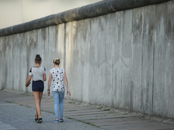 BERLIN, GERMANY - AUGUST 06:  Visitors walk along a surviving section of the former Berlin Wall at the Bernauer Strasse memorial on August 6, 2014 in Berlin, Germany. Germany will commemorate the 25th anniversary of the fall of the Berlin Wall, which was one of the many, sweeping events across central and eastern Europe as the Cold War came to an end, in November. The Berlin Wall, built by the communist authorities of the former East Germany, divided the city from 1961 until 1989. At least 138 people were killed while trying to flee from East Berlin into West Berlin.  (Photo by Sean Gallup/Getty Images)