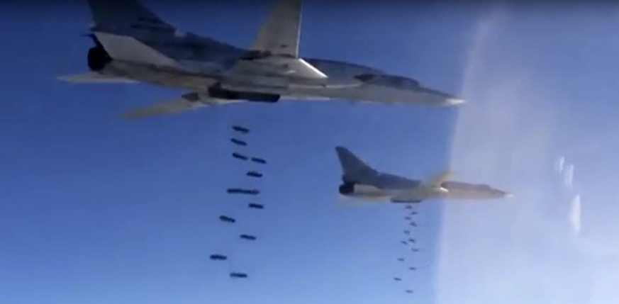 In this photo made from video released from Russian Defense Ministry official website on Friday, Nov. 20, 2015, Russian air force Tu-22M3 bombers drop bombs on a target in Syria as part of a Russian air campaign against targets in Syria, according to information provided by Russian Defense Ministry. Russian long-range bombers and navy ships have launched 101 cruise missiles in four days, including 18 fired by Russian navy ships from the Caspian Sea on Friday, according to information released by Russian Defense Ministry. (AP Photo/ Russian Defense Ministry Press Service)