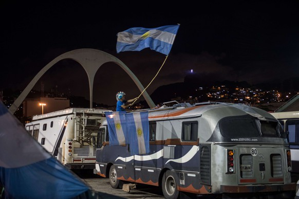 TO GO WITH AFP STORY BY CLAIRE DE OLIVEIRA  An Argentina's fan drinks beer and waves a national flag ontop his motorhome inside the Sambadrome that is opened to fans to park and camp for the final match between Argentina and Germany of the FIFA World Cup 2014 in Rio de Janeiro, Brazil, on July 11, 2014. AFP PHOTO / YASUYOSHI CHIBA