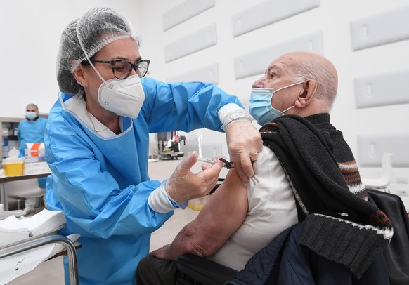 epa09095736 An enderly person is given a dose of the Covid-19 vaccine by a healthcare personnel at a vaccination center in Binasco, near Milan, Italy, 25 March 2021  EPA/DANIEL DAL ZENNARO
