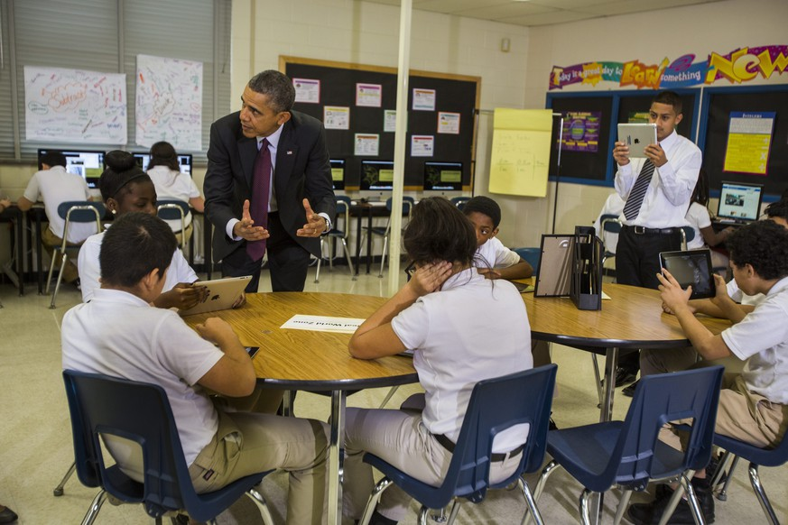 epa04055007 US President Barack Obama (L) tours a seventh grade classroom that uses technology to enhance students' learning experience, prior to delivering remarks on the ConnectED Initiative at Buck Lodge Middle School in Adelphi, Maryland, USA, 04 February 2014. ConnectED is President Obama's initiative to bring all schools into the digital age with broadband and wireless technology.  EPA/JIM LO SCALZO