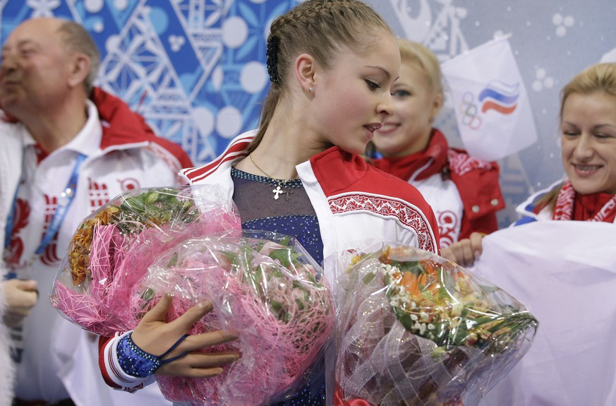 Yulia Lipnitskaya of Russia holds flowers given to her by spectators after competing in the women's team short program figure skating competition at the Iceberg Skating Palace during the 2014 Winter Olympics, Saturday, Feb. 8, 2014, in Sochi, Russia. (AP Photo/Darron Cummings, Pool)