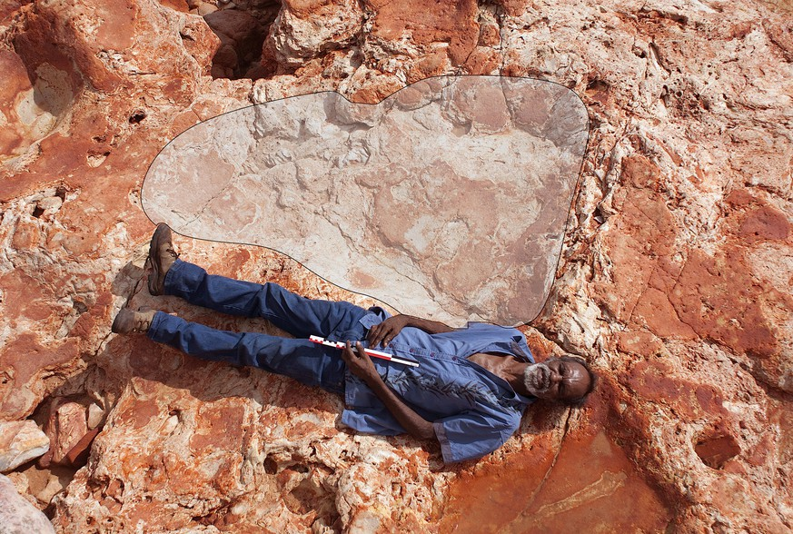 A supplied image of Aboriginal elder and Goolarabooloo Law Boss Richard Hunter alongside a 1.75m sauropod dinosaur track in the Lower Cretaceous Broome Sandstone, Walmadany area, Dampier Peninsula, in Western Australia, March 26, 2017. Picture taken March 26, 2017.       Damian Kelly-University of Queensland/Handout via REUTERS    ATTENTION EDITORS - THIS IMAGE WAS PROVIDED BY A THIRD PARTY. EDITORIAL USE ONLY. NO RESALES. NO ARCHIVE.