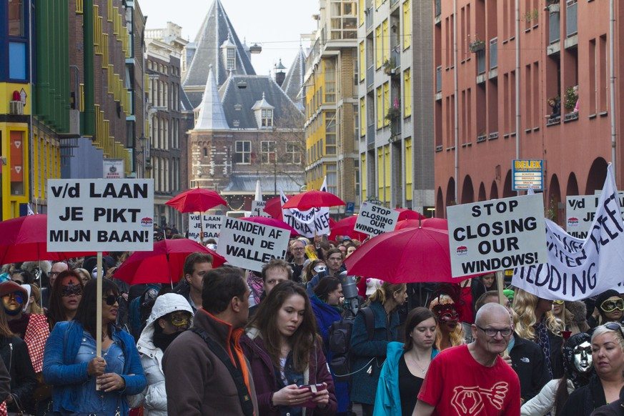 Prostitutes and sympathizers take to the streets to protest plans to clean up the city's famed red light district by shuttering windows where scantily-clad sex workers pose to attract clients,  in Amsterdam, Netherlands, Thursday, April 9, 2015. Prostitutes say that the closures are depriving them of safe places to work. (AP Photo/Peter Dejong)