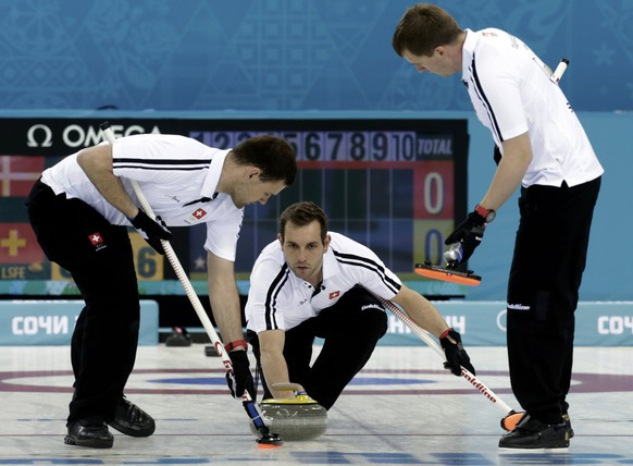 Switzerland's skip Sven Michel (C) delivers a stone between teammates Sandro Troillet (L) and Simon Gempeler during their men's curling round robin session game against Denmark t the 2014 Sochi Olympics in the Ice Cube Curling Center in Sochi February 15, 2014.     REUTERS/Ints Kalnins (RUSSIA  - Tags: SPORT OLYMPICS SPORT CURLING)