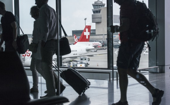 ZUR HEUTIGEN VEROEFFENTLICHUNG DER PASSAGIERZAHLEN 2014 DER SWISS STELLEN WIR IHNEN FOLGENDES BILDMATERIAL ZUR VERFUEGUNG ---  Passengers are on the way to and from the aeroplanes at Zurich Airport, pictured in Kloten, Switzerland, on July 31, 2014. (KEYSTONE/Christian Beutler)