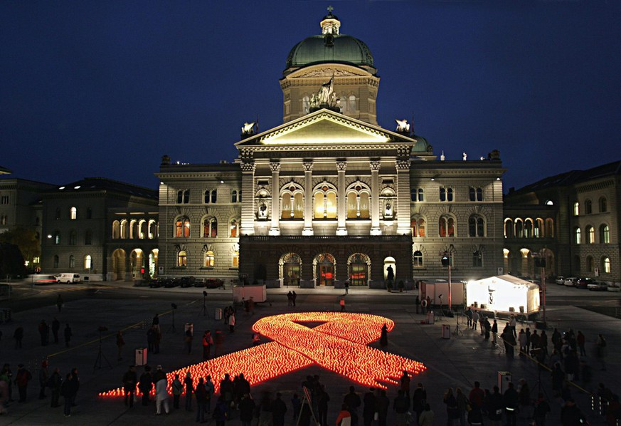 Organized by different Swiss aid organisations 6 000 candles, forming a ribbon, the symbol for solidarity with Aids patients, have been set alight on the Federation Square (Bundesplatz) in front of the government's building in Bern, Switzerland, Wednesday, December 1, 2004, on the occasion of the World Aids Day. The candles symbolize the 6 000 victims who daily die in Africa because of Aids. (KEYSTONE/Monika Flueckiger)